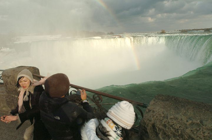 Tourists look over the brink of the Horseshoe Falls at Niagara Falls, Ontario, near where a man plunged over the falls and su