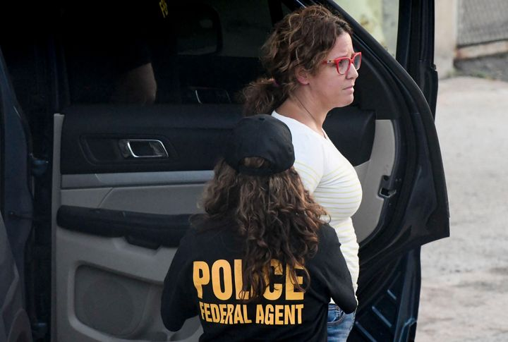 A federal agent escorts education contractor Mayra Ponce-Mendoza who was arrested in San Juan, Puerto Rico, Wednesday, July 1
