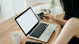 Woman with credit card and laptop paying bills online  at home