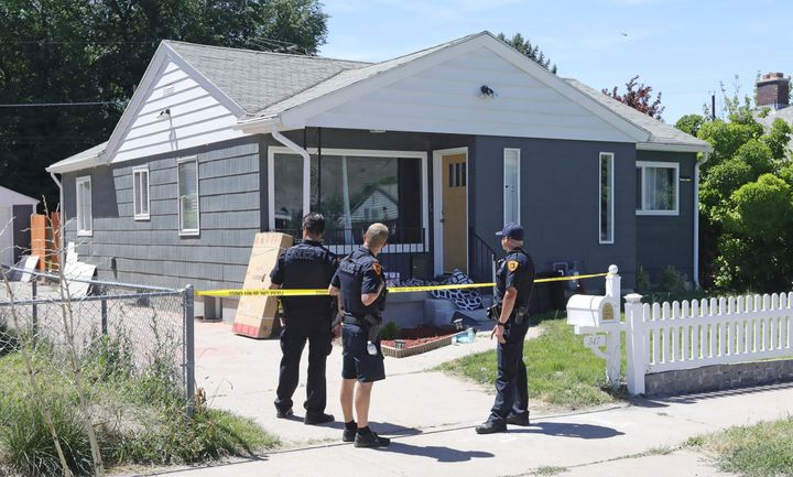 Police officers stand in front of the home of Ayoola A. Ajayi on June 28 in Salt Lake City.