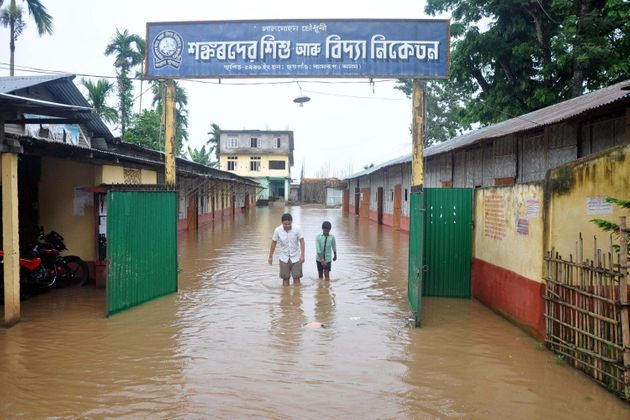 School students outside their partially submerged school at Chhaygaon in Kamrup District of Assam on...
