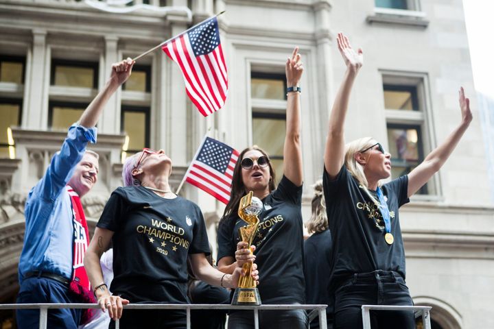 Alex Morgan, center, holds the World Cup trophy with teammate Megan Rapinoe at the parade.