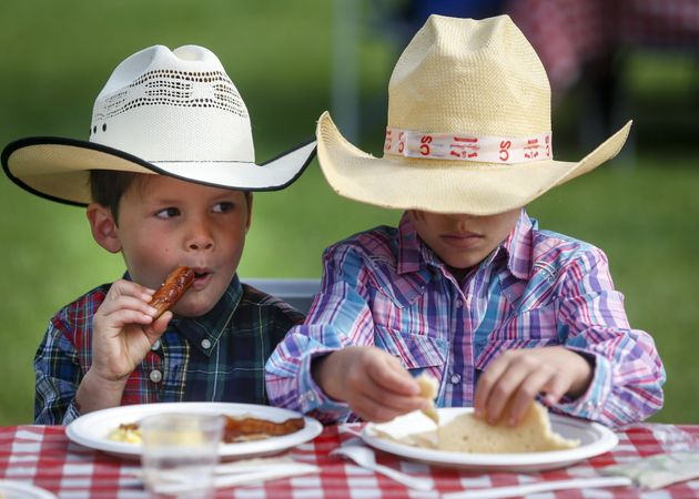 Two young boys enjoy a hot breakfast at the Stampede in Calgary on July 6,