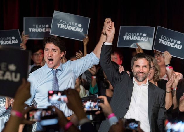 Prime Minister Justin Trudeau raises the hand of Steven Guilbeault during an event to...