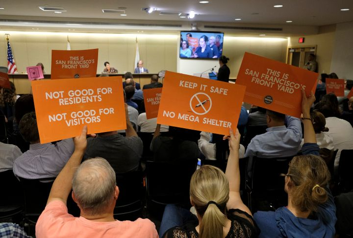 People opposed to a proposed homeless shelter hold up signs during a meeting of the Port Commission, April 23, 2019, in San F