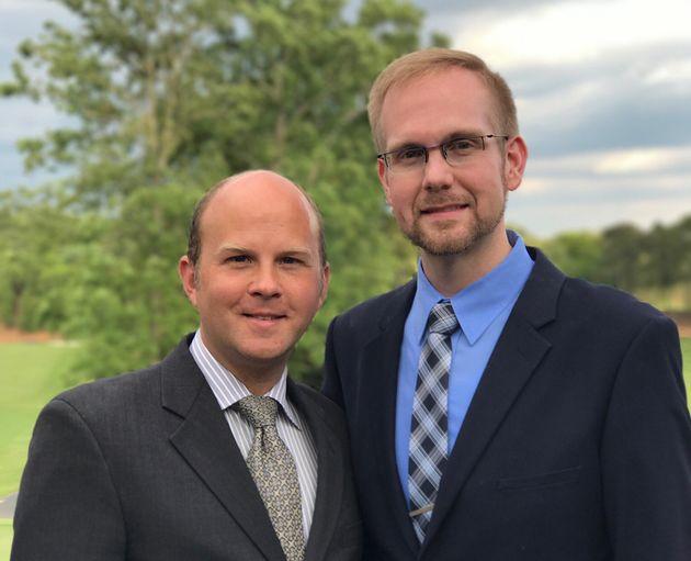 Joshua Payne-Elliott (right) and his husband, Layton Payne-Elliott, were both employed as Catholic school...