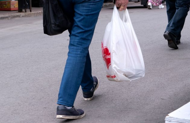 A woman carries a plastic shopping