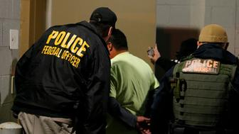 FILE - In this Oct. 22, 2018, file photo U.S. Immigration and Customs Enforcement agents escort a target to lockup during a raid in Richmond, Va. Carrying out President Donald Trump's hard-line immigration policies has exposed ICE to unprecedented public scrutiny and criticism, even though officers say they're doing largely the same job they did before the election, prioritizing criminals. (AP Photo/Steve Helber, File)