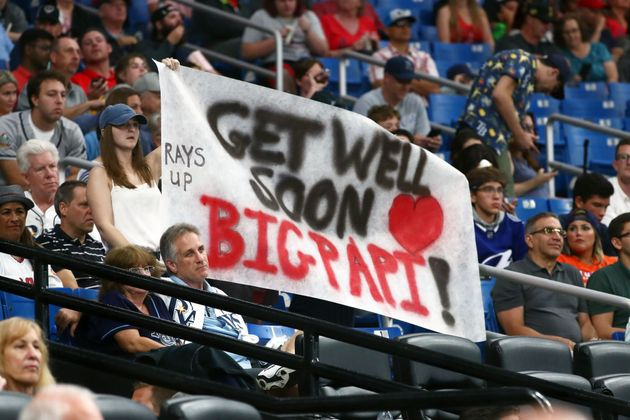 Baseball fans hold up a sign for former Boston Red Sox designated hitter David Ortiz during a game between...