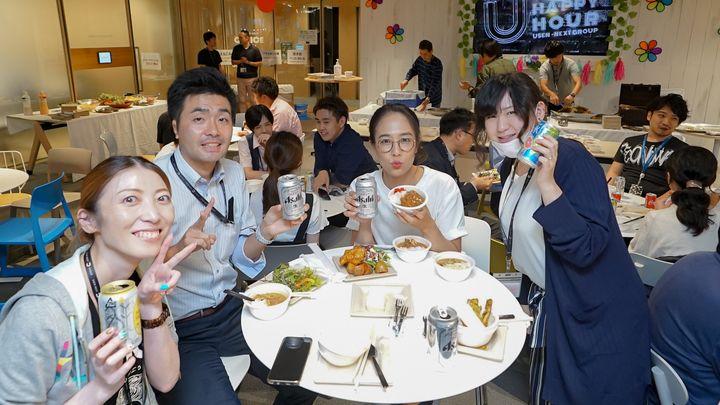 食事とアルコールを楽しむ社員たち