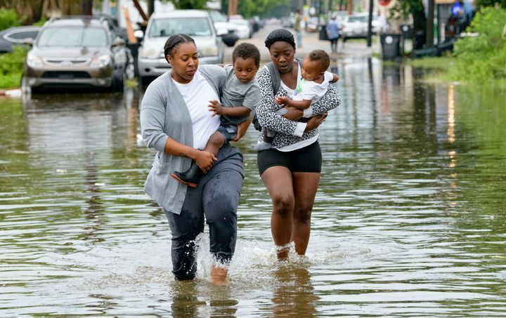 Jalana Furlough carries her son Drew Furlough as Terrian Jones carries Chance Furlough in New Orleans after flooding Wednesda