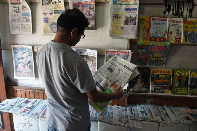 A Kashmiri man reads a newspaper at a stall in