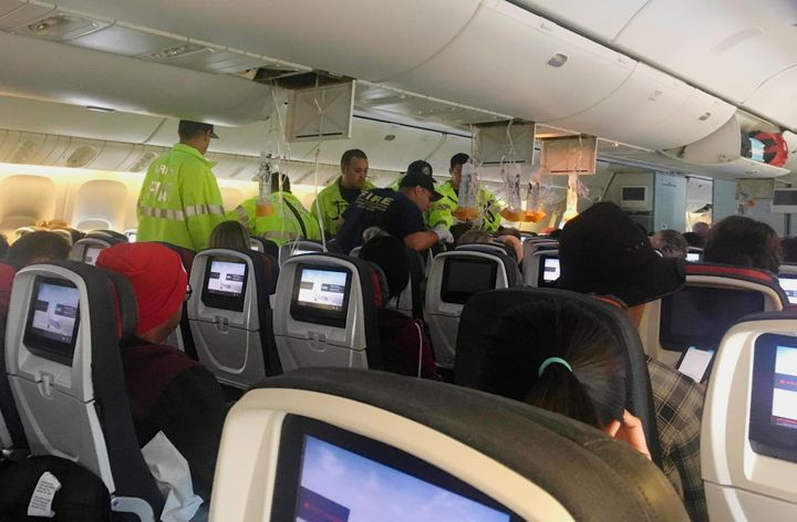 First responders are seen here treating a passenger on an Air Canada flight to Australia that was diverted on Thursday due to turbulence.