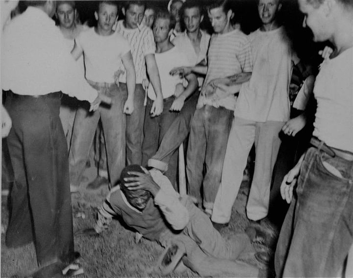 Surrounded by a group of white youths, an unidentified black man grimaces as a policeman tries to halt an attack on him in St