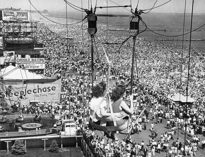 Passengers on the Parachute Jump ride see throngs of people on the boardwalk and beach at the Coney Island Amusement Park in