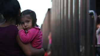 A migrant mother and child wait for a freight train to ride on their way north, in Salto del Agua, Chiapas state, Mexico, Monday, June 24, 2019. Mexico has deployed 6,500 National Guard members in the southern part of the country, plus another 15,000 soldiers along its northern border in a bid to reduce the number of migrants traveling through its territory to reach the U.S. (AP Photo/Marco Ugarte)