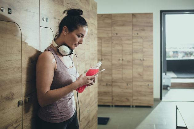 Athletic woman typing message on cell phone after sports training in locker room at health