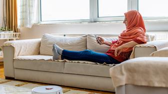 muslim woman watching movie on cell phone while working at home cleaning roboto