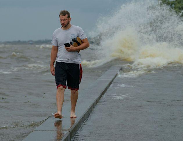 Un homme marche sur Lakeshore Drive, à Mandeville, en Louisiane, avant l'arrivée de l'ouragan...