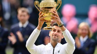 Serbia's Novak Djokovic raises the winner's trophy after beating Switzerland's Roger Federer during their men's singles final on day thirteen of the 2019 Wimbledon Championships at The All England Lawn Tennis Club in Wimbledon, southwest London, on July 14, 2019. (Photo by Daniel LEAL-OLIVAS / AFP) / RESTRICTED TO EDITORIAL USE        (Photo credit should read DANIEL LEAL-OLIVAS/AFP/Getty Images)
