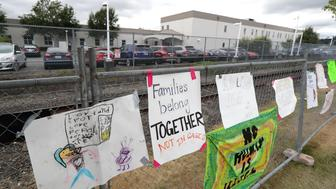 "A sign that reads ""Families belong Together Not in Cages"" hangs on a fence outside the Northwest Detention Center in Tacoma, Wash., Tuesday, July 10, 2018. The Trump administration rushed to meet a deadline Tuesday for reuniting dozens of youngsters forcibly separated from their families at the U.S.-Mexico border. (AP Photo/Ted S. Warren)"