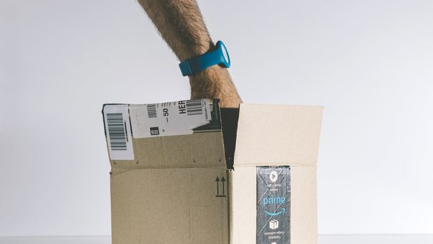 Paris: Male hand searching for product inside the open Amazon Prime logotype printed on cardboard box side. Amazon is an American electronic e-commerce company distribution worlwide e-commerce goods