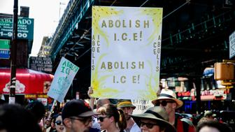 People hold signs calling for the abolition of Immigration and Customs Enforcement at a rally before the start of a march in opposition to the Trump administration's plans to continue with raids to catch immigrants in the country illegally, Sunday, July 14, 2019, in the Queens borough of New York. (AP Photo/Julius Constantine Motal)