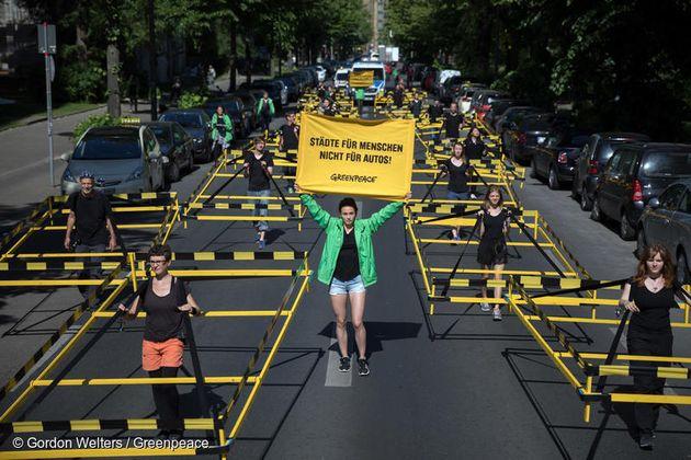도로의 자동차가 차지하는 공간을 보여주는 행진. 그린피스 활동가가 '차가 아닌 사람을 위한 도시' 라는 사인을 들고
