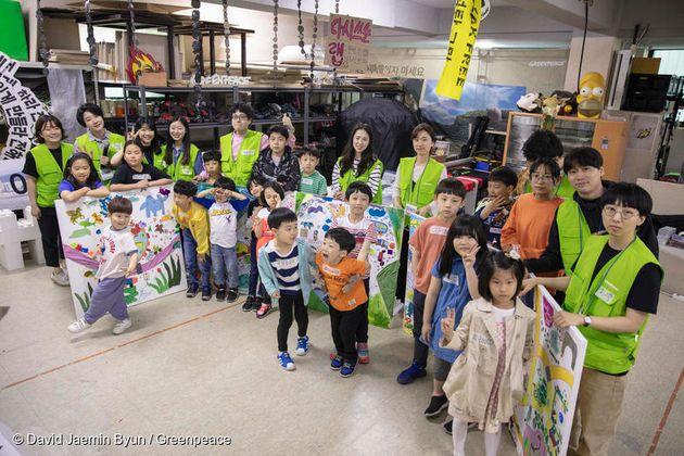 아이들과 그린피스 활동가가 함께 완성한 '미래 교통의 모습' 그림 앞에 서