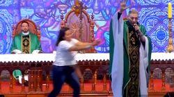 Una mujer empuja a un sacerdote en plena