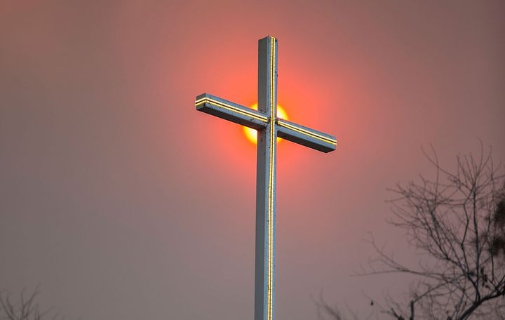 Smoke from a wildfire in California appears behind a church cross.
