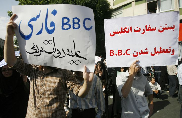 Supporters of President Mahmoud Ahmadinejad hold up placards against the British media during a rally in Tehran's Vali Asr Sq