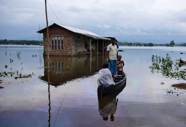 Villagers are transported on a boat towards a safer place at a flooded village in Nagaon district, in...