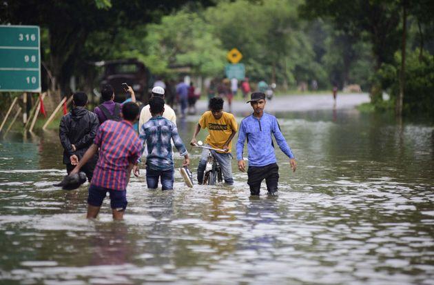 People cross flooded Narional Highway 37 at Bagaori Near Kaziranga National Park, Assam, July 15,