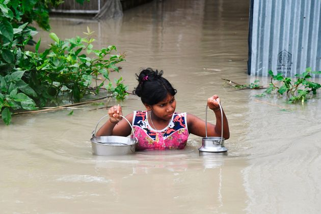A girl carries drinking water as she wades through flood waters at Pabhokathi village in Morigaon district...
