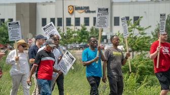 Some workers, supporters and activists picket outside the Amazon fulfillment Center in Shakopee, Minn. on Monday, July 15, 2019. At the warehouse workers planned the strike to raise awareness for workers' conditions. (Glen Stubbe/Star Tribune via AP)