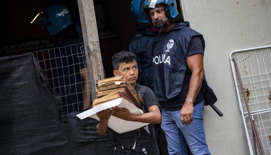 Il bambino porta via i libri e il poliziotto lo guarda: la foto simbolo dello sgombero di Primavalle scuote la