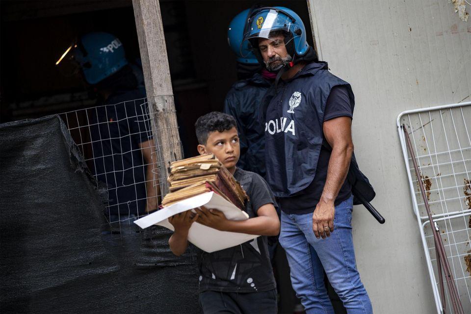 Il bambino porta via i libri e il poliziotto lo guarda: la foto simbolo dello sgombero di Primavalle...