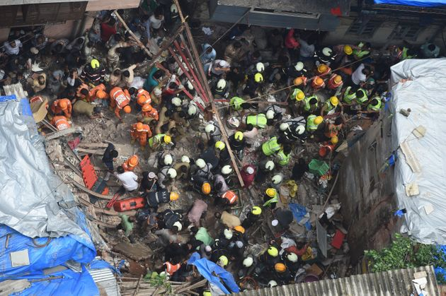 Fire brigade personnel and rescue workers look for survivors after a building collapsed in Mumbai on...
