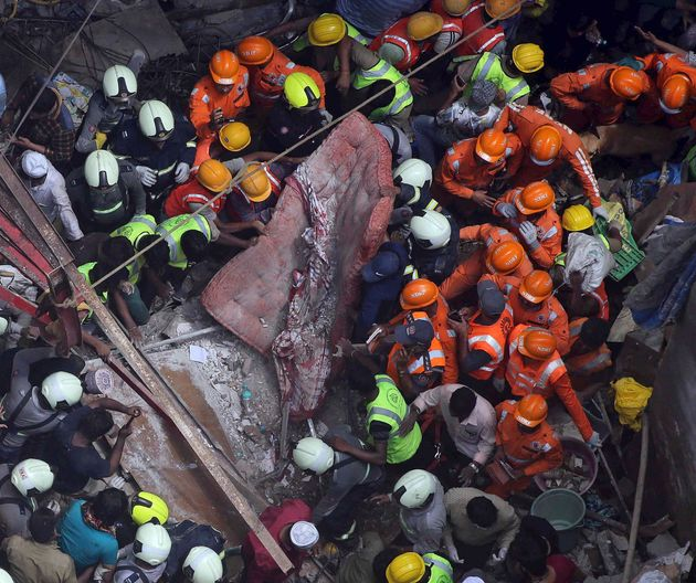 Rescuers work at the site of a building that collapsed in Mumbai, on July 16,