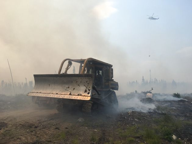 A bulldozer clears debris as crews battle a forest fire in northern Ontario near Pikangikum First Nation...