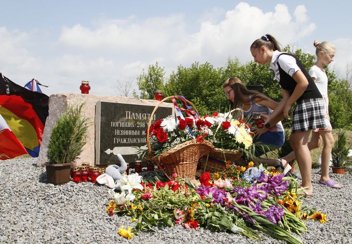 People gather near a monument to the victims of the crash in the Donetsk Region, Ukraine.