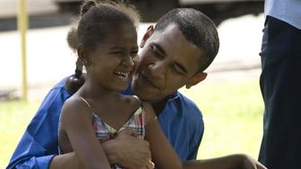 BEAVERDALE, IA - JULY 4: U.S. Senator Barack Obama holds his youngest daughter Sasha before speaking at an Independence Day celebration on July 4, 2007 in Beaverdale, Iowa. Obama, on a two-day campaign tour through Iowa, announced this weekend that his campaign had raised 32.5 million dollars in the second quarter.  (Photo by David Lienemann/Getty Images)