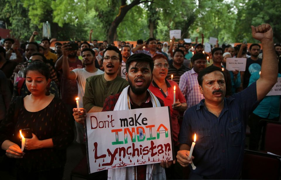 protesters shout slogans as they hold placards and candles during a protest condemning recent mob lynching...