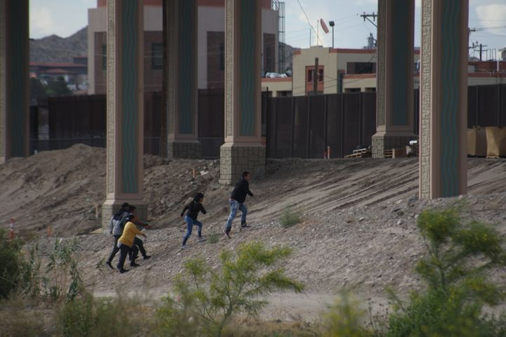 Migrants cross the Rio Bravo from Ciudad Juarez, Mexico to El Paso, Texas, to surrender to the Border Patrol on 8 May 2019.