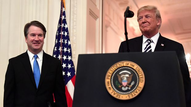 President Donald Trump, right, smiles as he stands with Supreme Court Justice Brett Kavanaugh, left, before a ceremonial swearing in in the East Room of the White House in Washington, Monday, Oct. 8, 2018. (AP Photo/Susan Walsh)