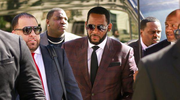 En esta foto del 26 de junio del 2019, el cantante de R&B R. Kelly, en el centro, llega a la Corte Penal de Leighton para responder a delitos de abuso sexual en Chicago. Kelly, quien ya enfrenta cargos de abuso sexual en Illinois, fue arrestado en Chicago el jueves 11 de julio del 2019 bajo un acta de un jurado de instrucción federal que incluye 13 cargos, entre ellos crímenes sexuales y obstrucción de la justicia. (AP Foto/Amr Alfiky, Archivo)