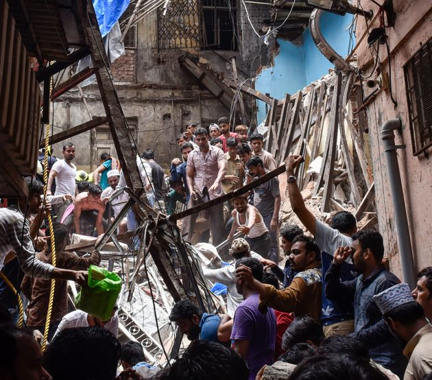 Rescuers work at the site of a building that collapsed at Dongri on July 16, 2019 in