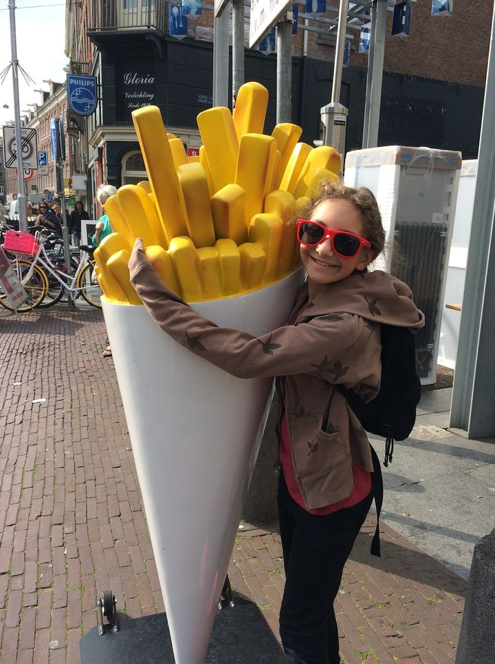 Sammi hugging a statue of french fries during a family trip to Amsterdam.