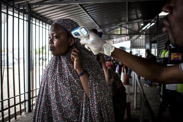 A woman gets her temperature measured at an Ebola screening station as she enters the Democratic Republic...